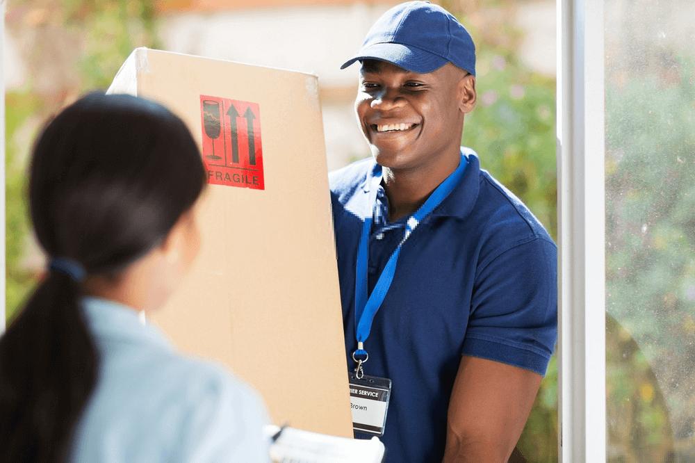 Envoyer un colis au Cameroun avec J'enlève Je Livre : un livreur remettant un colis à sa destinataire