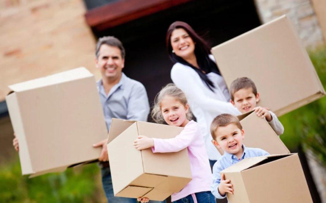 Famille portant des cartons de déménagement : 6 erreurs à éviter quand on déménage avec des enfants