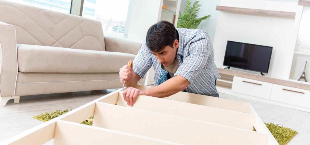 Un homme démonte un meuble