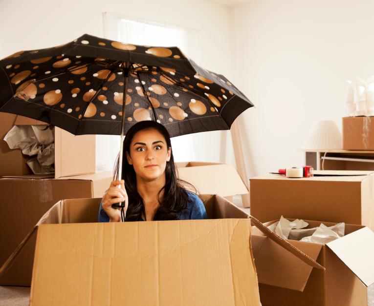 Femme sous un parapluie avec ses cartons de déménagement